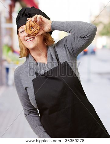 Middle aged cook woman looking through a donut at street