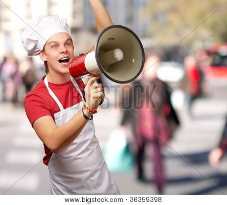 portrait of young cook man shouting with megaphone at crowded street
