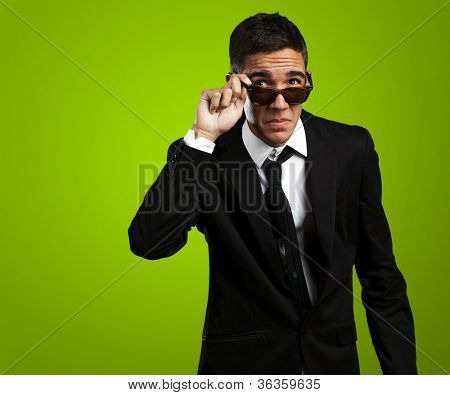 portrait of business man taking off the sunglasses against a green background