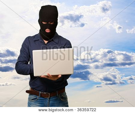 young male thief holding laptop, outdoor