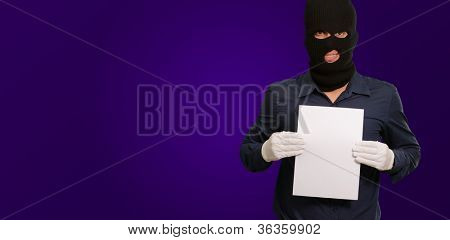 Man wearing a robber mask showing a blank paper on purple background