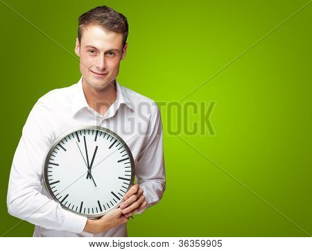 Happy Man Holding Clock In His Hand On Green Background