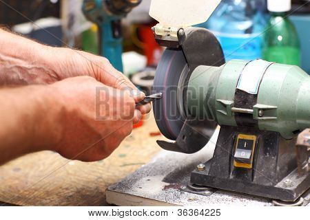 Detail of hands working on sharpening machine tool