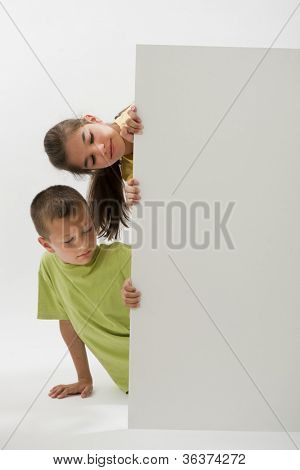 Two children holding a blank sign and looking at it; you can add your own text
