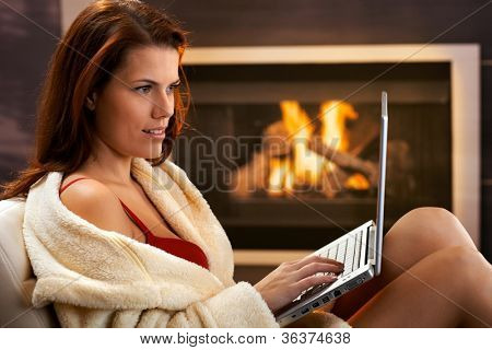 Winter portrait of sexy young woman using laptop computer in bathrobe and red bra in front of fireplace, smiling.