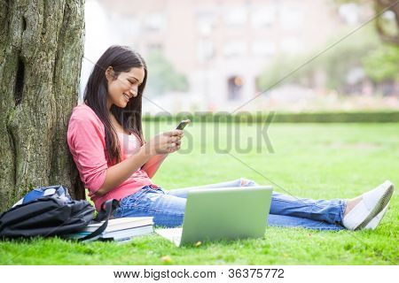 A beautiful hispanic college student texting on her cellphone