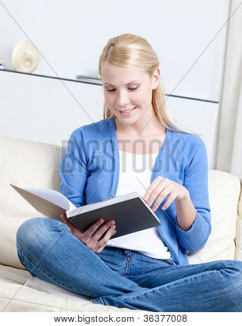 Beautiful woman reads the book lying on the white leather sofa