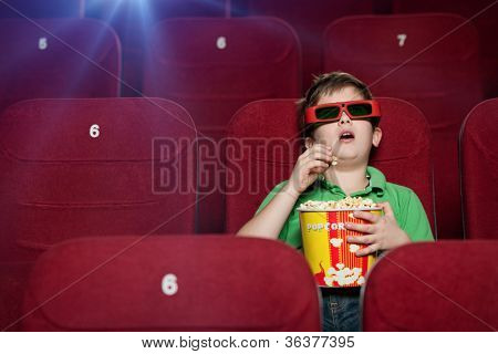 Surprised boy eating popcorn in the movie theater