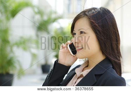 Young Asian business woman talking phone outside modern building