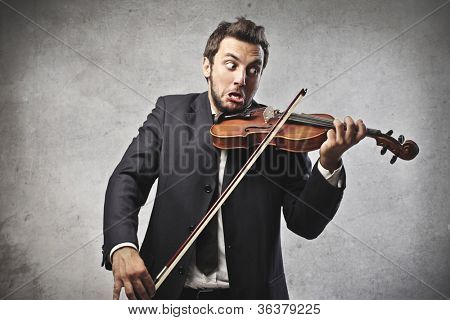 Young businessman trying to play the violin