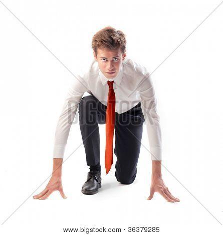 Empresario joven aislado de rodillas como si a punto de comenzar una carrera