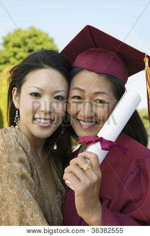 Portrait of a happy mature female graduate holding degree with daughter