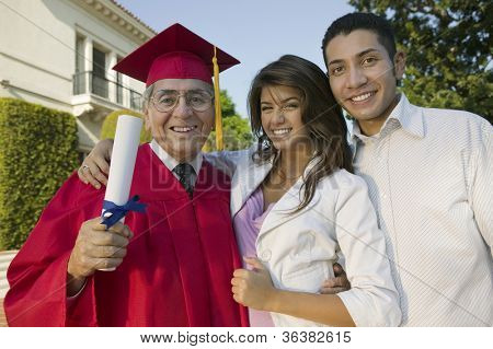 Portrait of an excited senior male graduate with family holding degree