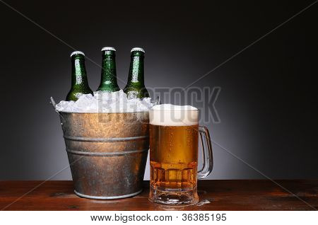 An ice bucket with three green beer bottles next to a full mug of ale on a wet wood surface. Horizontal format with a light to dark gray background.
