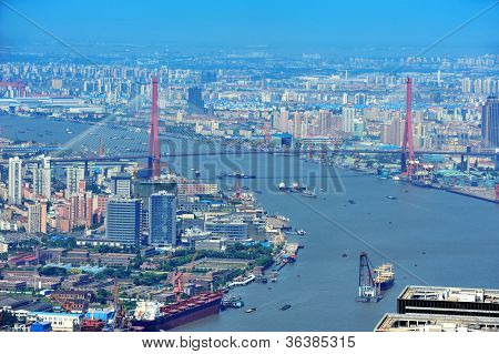 Shanghai city aerial view with urban architecture over river and blue sky in the day.