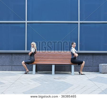 Quarrel between two business women  sitting on the bench