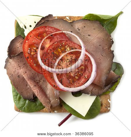 Sliced roast beef on a multigrain cracker, with Swiss cheese, spinach, tomato, and red onion.  Isolated on white.