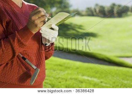 Midsection of a senior woman writing golf score on scorecard