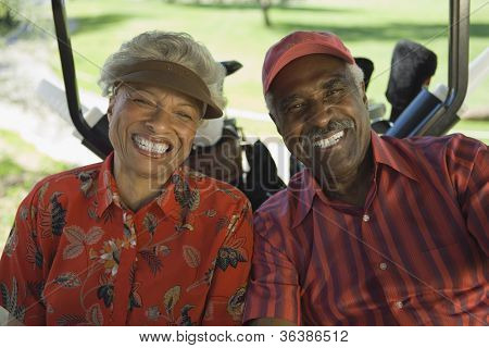 Portrait of a happy African American couple in golf cart