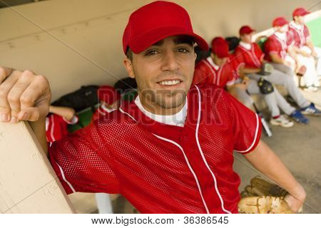 Portrait of a baseball player smiling with team in background