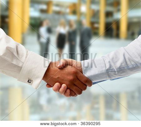 Apretón de manos frente a empresarios