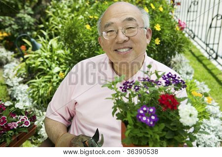 Portrait of a happy senior man gardening in his own garden