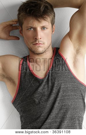 Handsome young man with arms up and sexy expression