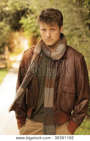 Young handsome man in autumn  outdoor setting wearing fashionable clothing