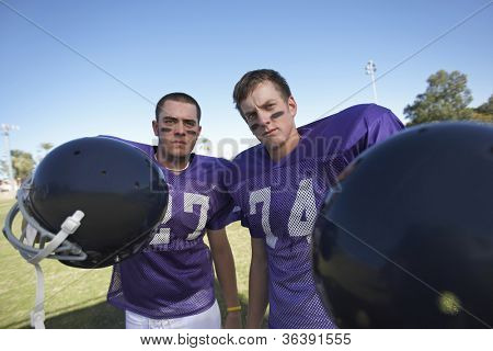 Portrait of young american football players standing together holding helmets