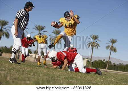 American football player trying to block rivalry team member while referee watching on field