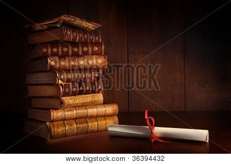 Pile of old books and diploma on desk