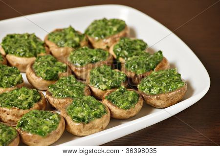 A picture od champignon mushrooms stuffed with spinach and served on a white plate over wooden background