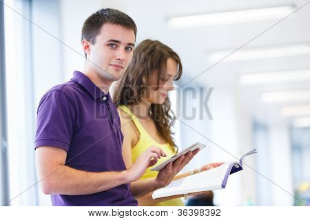 Two college students in library, reading books, using tablet computer (color toned image; shallow DOF)