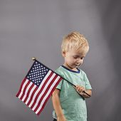 Young Boy Holds Flag On Shoulder