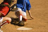 picture of softball  - Female softball player sliding into base with baseman in the foreground - JPG