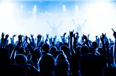 stock photo of crowd  - cheering crowd in front of bright stage lights - JPG