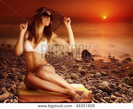 Sexy modelo bronzeado posando na praia no fundo dramático vermelho do pôr do sol, litoral rochoso, névoa mais s