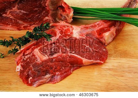 raw meat : boned fresh ribs served with thyme and green chives on wooden board isolated over white background