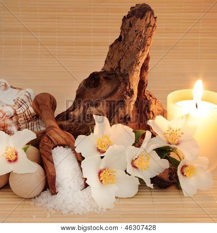 Spa still life of mock orange flower blossom, with sea salt, conch shell, wooden bath balls and  driftwood, lit with candlelight over bamboo.  Philadelphus mexicanus.