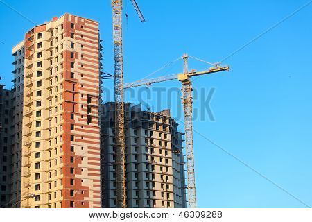 Construction Of Highrise Buildings With Cranes. Blue Sky Background