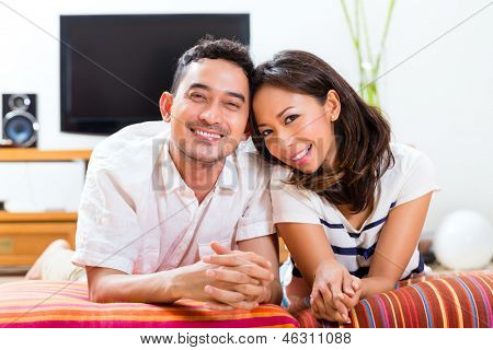 Young Indonesian couple - man and woman - sitting at home on a couch, it's weekend and they enjoying the leisure time