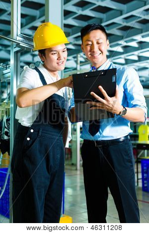 Worker or production manager and owner, ceo or controller, look on a Clipboard in a Chinese factory
