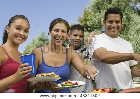 Portrait of a boy with happy family gathered around the grill at picnic