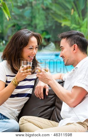 Young Indonesian couple - man and woman - at home, drinking together and clinking glasses