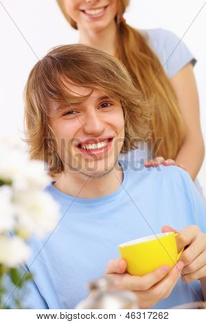 Young happy man drinking tea at home