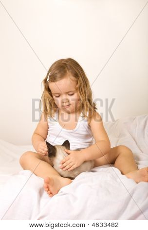 Little Girl Sitting In Bed With Her Kitten