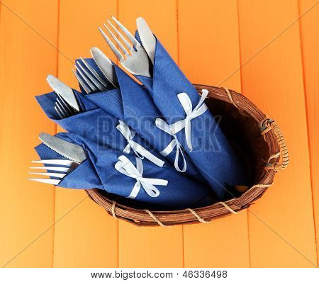 Forks and knives wrapped in blue paper napkins, in basket,  on color wooden background