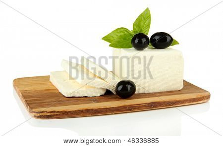 Sheep milk cheese with basil  and black olives, on cutting board, isolated on white