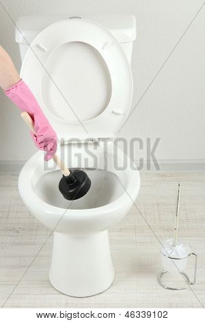 Frau verwendet einem Kolben, ein WC-Becken im Badezimmer Sprünge zu helfen