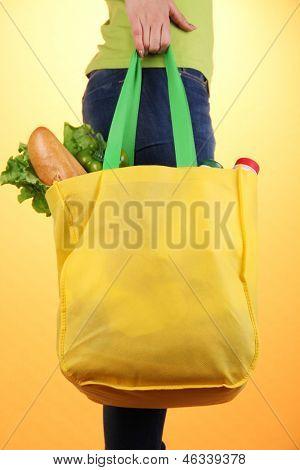 Girl with shopping bag on orange background